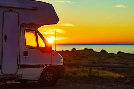 Camper rv at sunrise on mediterranean coast in Spain. Camping on nature beach. Vacation and trip in motor home.