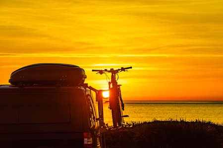 Camper, recreational vehicle with bicycles on rack camping on beach at sunrise. Holidays and travel in motorhome.