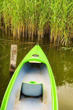 Boat in calm lake shore. Summer activity.