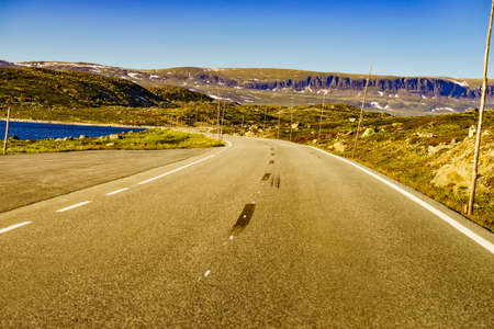 Road crossing Hardangervidda plateau, Norway landscape. National tourist Hardangervidda route.