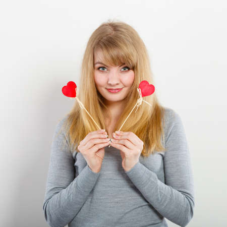 Love and fun concept. Lovely enjoyable smiling woman playing with two little red hearts on sticks. Playful joyful attractive blonde girl portrait. 写真素材