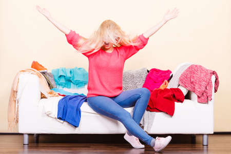 Clothing dilemmas concept. Blonde woman with windblown does not know what to wear sitting on messy couch with piles of clothes. Standard-Bild