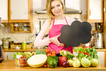 Woman in kitchen wearing apron having many vegetables on table holding speech bubble, thinking balloon black board with copy space. Healty eating, dieting concept.