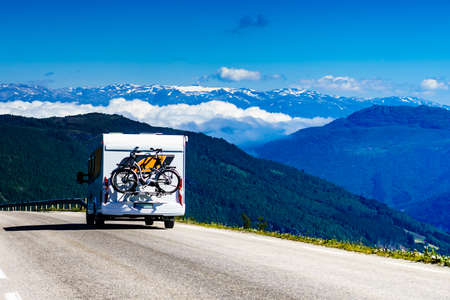 Camper car with bicycles on road trip in norwegian mountains. Traveling, holidays and adventure concept. Norway Scandinavia Europe.