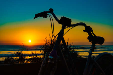 Bicycle outdoor parked on beach, evening time, sunset sky. Holidays, sport and recreation. 写真素材