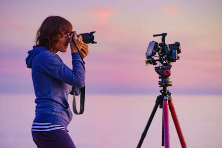 Tourist woman photographer with two cameras taking travel photo on nature at sunset time. 写真素材