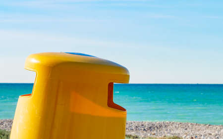 Seaside landscape. Spanish sea shore with yellow garbage bin or trash can. Keeping the beach clean. 写真素材