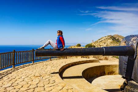 Tourist attraction. Woman at Battery de Castillitos in Spain Cartagena, Cabo Tinoso. Military cannon for coast defense, massive naval gun batteries. 写真素材