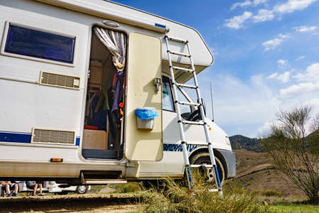 Camping on nature. Camper vehicle with portable ladder. Caravanning equipment, must have tool, maintain rv. Holiday trip with motor home.