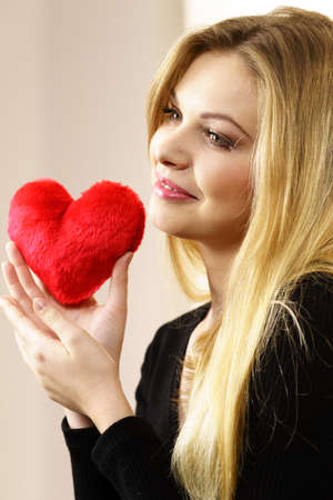 Romantic woman holding small red heart shaped fluffy pillow. Valentines day gift.