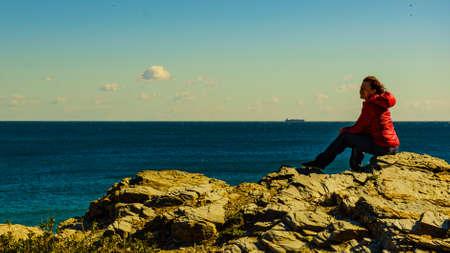 Tourist woman on spanish rocky coastline in Murcia region. Mediterranean Sea coast landscape, Calblanque Regional Park. 写真素材