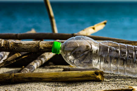 Plastic empty water bottle abandoned on beach sea shore. Environmental pollution global ecological problem. Earth ecology.