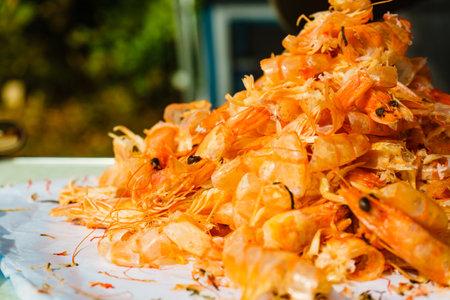 Seafood, ocean food. Pile of shrimps heads and shells. Peeling raw fresh shrimp. 写真素材