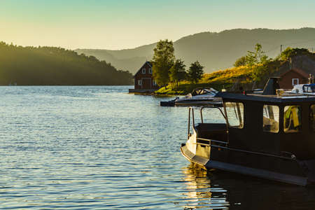 Wooden cabin house on water fjord shore. Summer landscape in Norway, Scandinavia