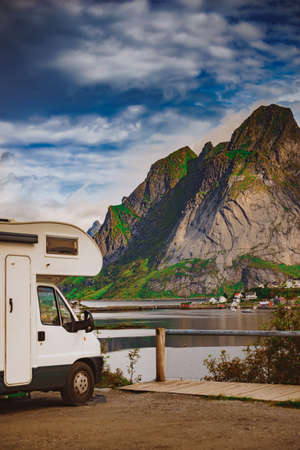 Camper car motor home and fjord landscape with Reine village in summer, Lofoten Norway. Camping on nature. Holidays and travel in caravan.