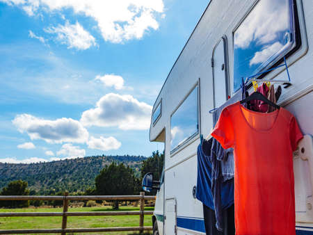 Wild camping on nature. Camper car rv with clothes hanging to dry. Holidays with motor home.
