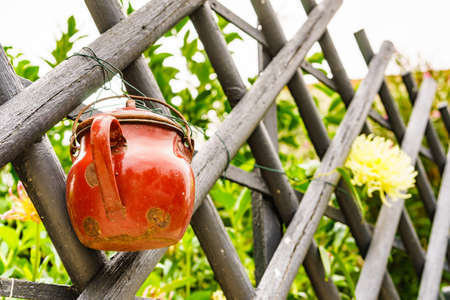 Old red pot hanging on country fence.