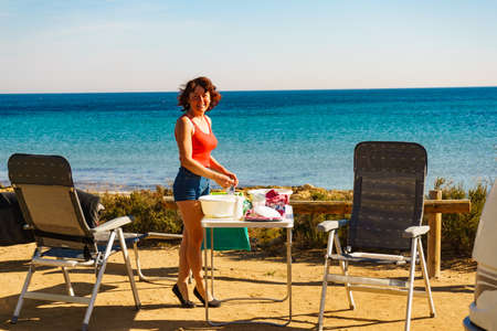 Mature woman washing up dishes in bowl on fresh air. Dishwashing outdoor on camping site, sea shore 写真素材