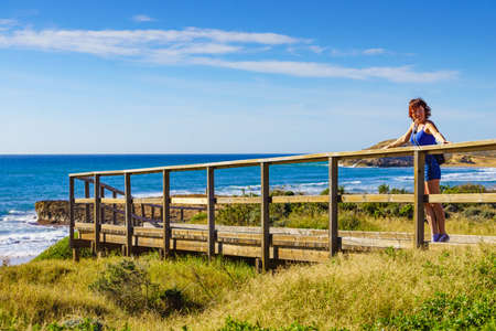 Tourist woman walking relaxing on beach seashore, enjoying sunlight. Cala Magre in Calblanque Regional Park, Murcia region Spain.