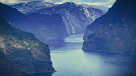 Amazing dramatic view of the fjords and mountains. Aurlandsfjord fjord landscape in Norway Scandinavia. National tourist road known as The snow road.