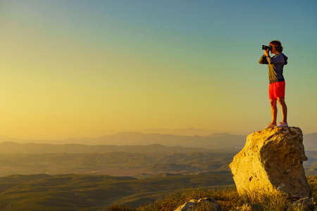 Tourist woman with camera taking travel photo from coastal spanish landscape, Mesa Roldan location in province Almeria, Andalusia Spain. Cabo de Gata Natural Park.