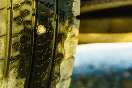 Broken tire because of nail pounding, closeup. 写真素材