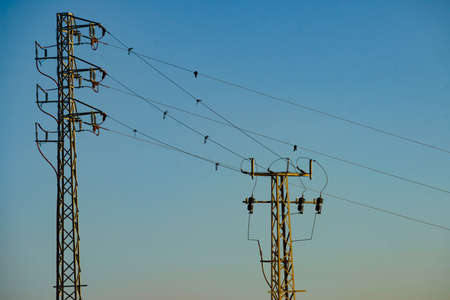 Electricity transmission pylons, power lines high voltage towers against blue sky.