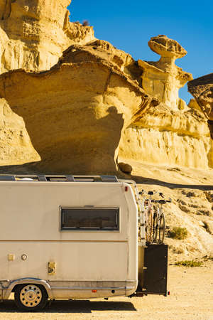 Camper car on parking area at eroded yellow sandstone formations, Enchanted City of Bolnuevo, Murcia Spain. Tourist attraction. 写真素材
