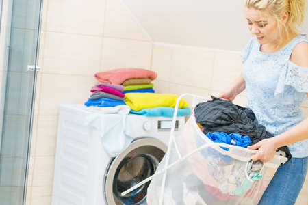 Woman having troubles with holding big laundry basket full of colorful dirty clothes. Bathroom utensils concept. 写真素材