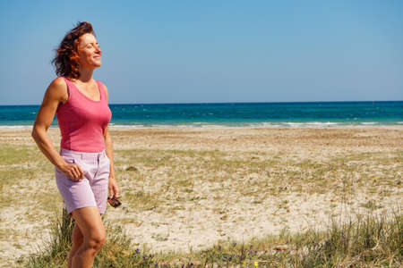 Mature woman walking on beach, relaxing at San Pedro del Pinatar park, Murcia Spain. Summer holidays.