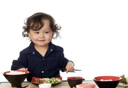 kelet ázsiai kultúra: Little boy eating asian food, isolated on a white background.