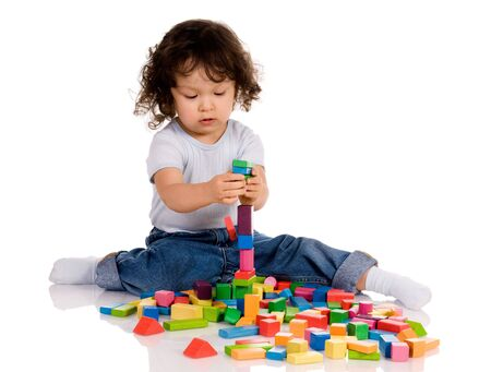 little boy playing with bricks photo