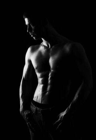 weightlifting: The male portrait  on black  background, low key Stock Photo