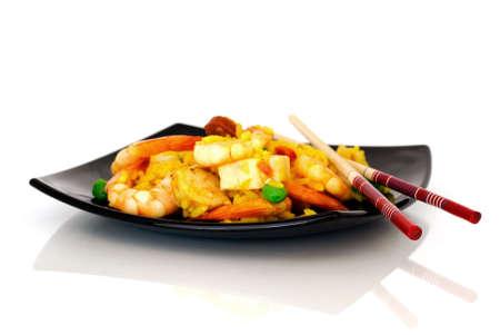 Chopsticks and paella on black plate Stock Photo