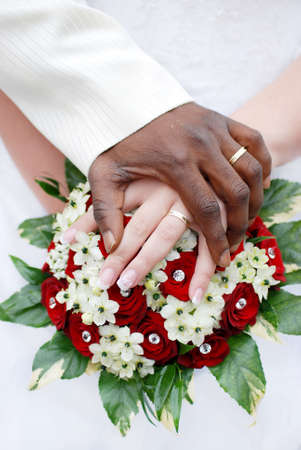 Wedding flowers and hands of a newly-married couple with wedding rings Stock Photo
