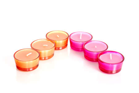 Pink and orange candles in glass isolated on white