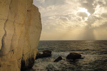 hanikra: Spectacular view of rays of light spewing from behind the clouds at the Israel bordering with Lebanon of Rosh HaNikra near the Grottoes
