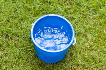 seau d eau: Collecte des eaux de pluie dans un seau bleu Banque d'images