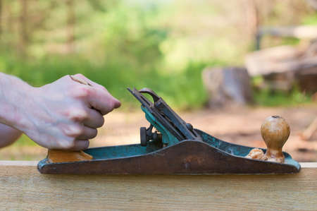 Hands of a carpenter planed wood. Work on the nature. Stock Photo