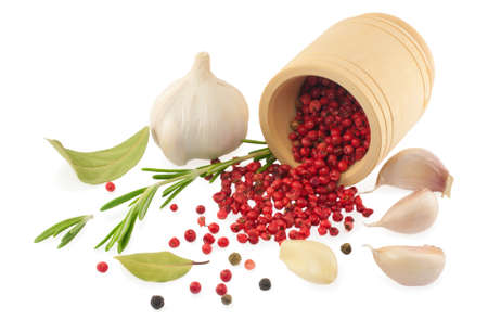 Rose pepper, garlic, herbs and spices in a mortar isolated on white. photo