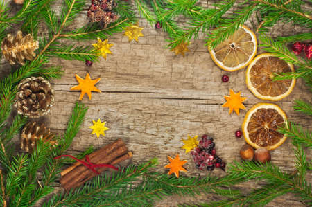 Christmas frame  fir branches, nuts, pine cones, Christmas berry, stars, cinnamon  on a wooden background photo