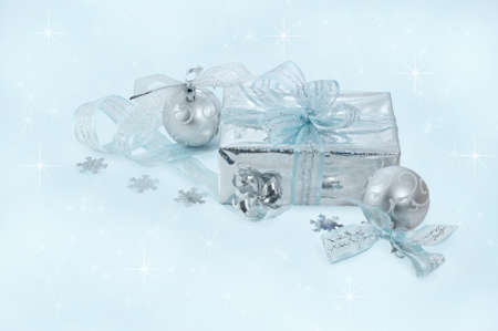 silver Christmas balls and gift wrapped in silver with blue ribbons on  soft blue background photo