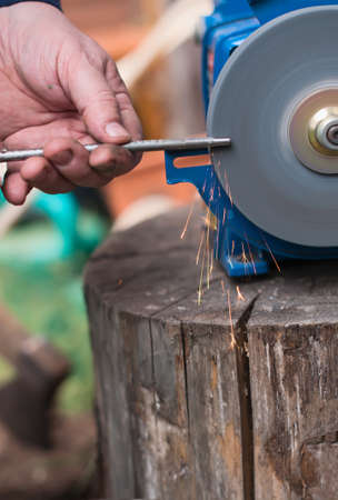 emery: Sharpening  of iron by abrasive disk machine. Male hands sharpen tool. Stock Photo