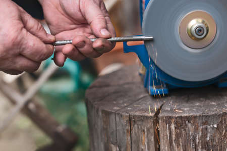 sharpen: Sharpening  of iron by abrasive disk machine. Male hands sharpen tool. Stock Photo