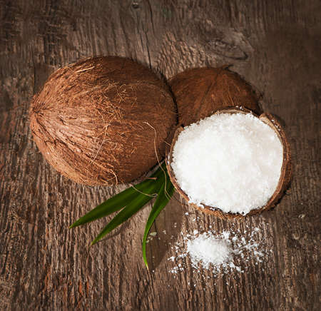 shredded coconut: Coconut and coconut shavings on an old wooden board Stock Photo