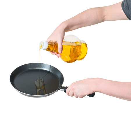 kitchen  cooking: Close-up of woman hand poured from a bottle of vegetable oil in a frying pan isolated on white. Stock Photo