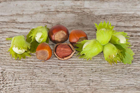 Hazelnut whole and chopped nuts on a wooden background.