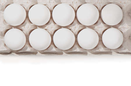 dozen: Ten fresh white eggs in a container, isolated on  white background, top view. Stock Photo