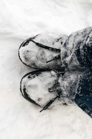 black boots: Black Boots and Blue Jeans in Fresh White Snow Stock Photo
