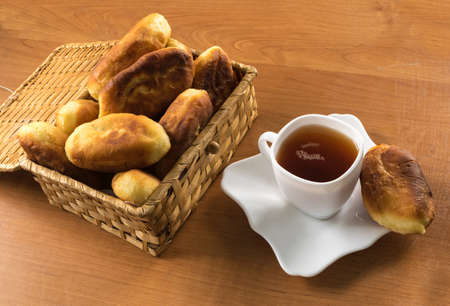 Traditional Homemade Baked Patties or Pies with Jam in a Wicker Basket next to a White Cup of Tea. Fried Russian Pirozhki made from Yeast Dough in Rustic Style Stock Photo